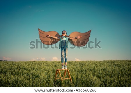 Happy kid playing. Child having fun outdoors. Kid with cardboard wings. Child in summer field. Travel and vacation concept. Imagination and freedom concept - stock photo