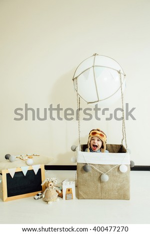 Happy kid playing in handmade basket of air balloon. Child having fun at home. Young pilot indoors at solid color background with copy space. Boy in hat looking away. Blank chalkboard. - stock photo