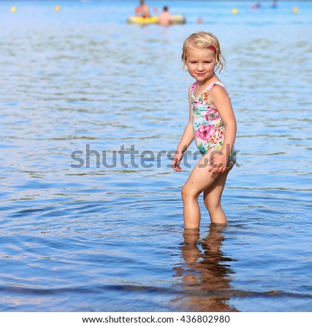 Happy kid playing in the lake. Healthy smiling toddler girl enjoying summer vacation outdoors.  - stock photo