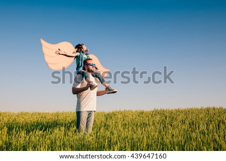 Happy kid playing with father. Dad and son outdoors. Father carrying child on his back. Happy family in summer field. Family having fun. Travel and vacation concept. Imagination and freedom concept