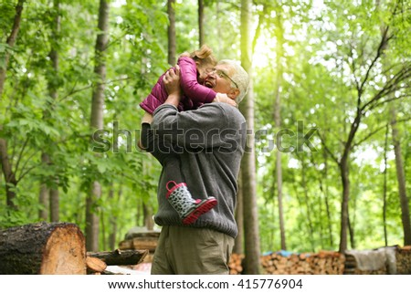 Happy kid playing with grandfather in the park. - stock photo