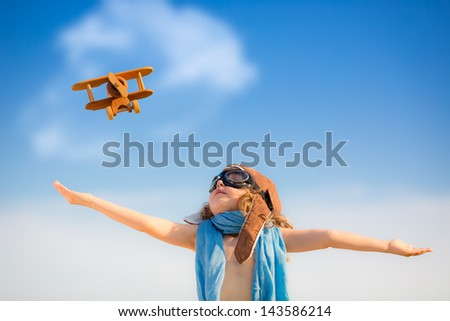 Happy kid playing with toy airplane against blue summer sky background - stock photo