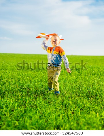 Happy kid playing with toy airplane against blue summer sky background.  Boy throw foam plane in green field. Best childhood concept.