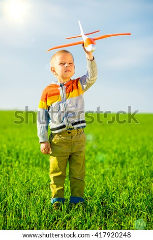 Happy kid playing with toy airplane against blue summer sky background.  Boy throw foam plane in green field. Best childhood concept. - stock photo
