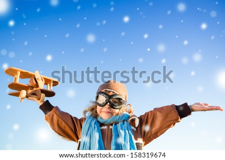 Happy kid playing with toy airplane against blue winter sky background