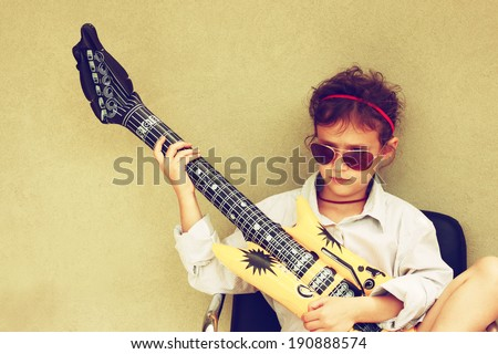 Happy kid playing with toy guitar. retro filter.  - stock photo