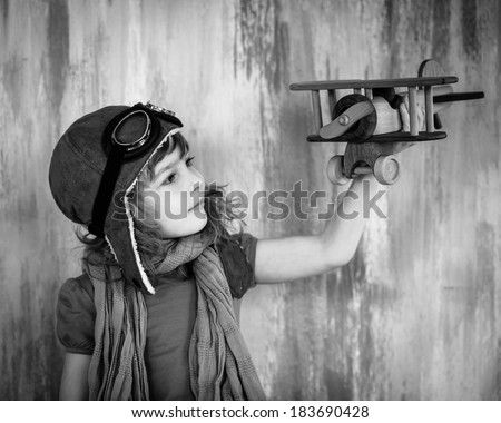 Happy kid playing with toy wooden airplane indoors. Black and white photo - stock photo