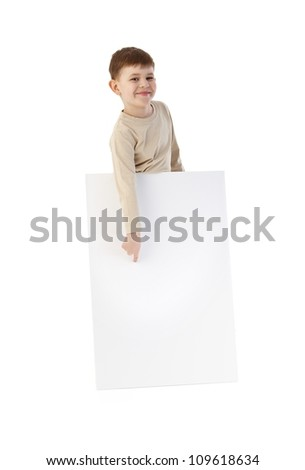 Happy kid pointing to blank sheet, smiling. - stock photo