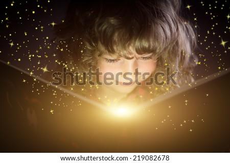 Happy kid reading magic book - stock photo