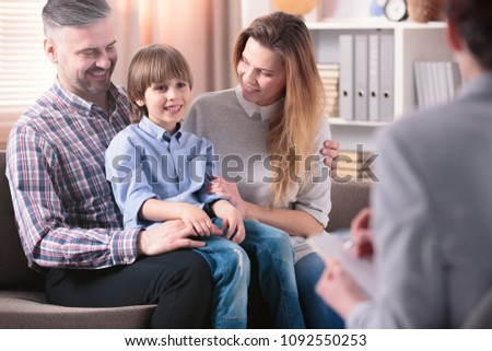 Happy kid sitting on his father's lap next to his mother during a meeting with school counselor