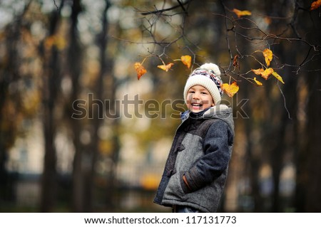Happy kid standing in autumn park. A boy in a cap and jacket laughs. Cold autumn day.