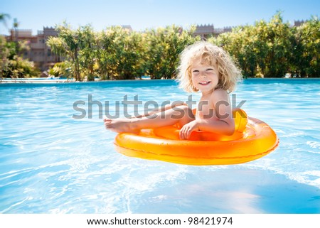 Happy kid swimming in blue water of pool on a tropical resort at the sea. Summer vacations - stock photo
