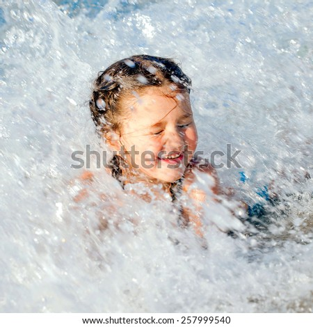 Happy kid swimming in the in sea foam among the waves. Summer holidays concept. - stock photo