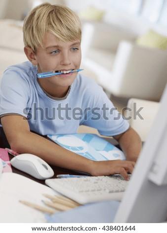 Happy kid using computer at home - stock photo