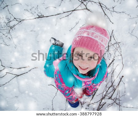 Happy kid winter day playing in the snow.  - stock photo