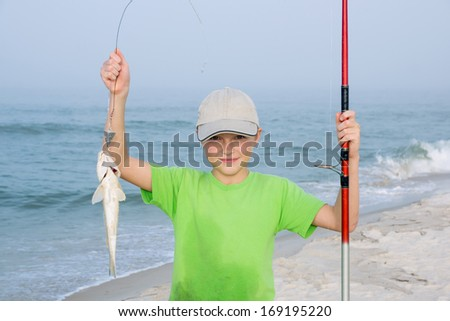 Happy kid with a fishing rod and fish  Gulf Kingfish.Background of the Gulf of Mexico. Focus on the child's face - stock photo