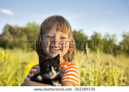 Happy kid with a kitten in her arms in nature - stock photo
