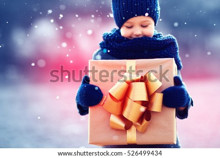 happy kid with big gift box under a snowfall. Focus on gift box