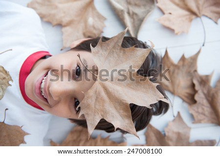 Happy kid with leaves - stock photo