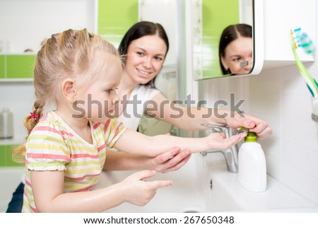 Happy kid with mom washing hands in the bathroom - stock photo
