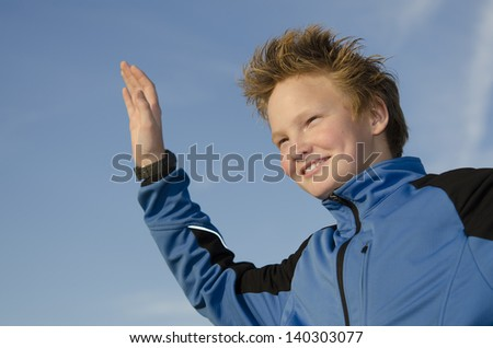 Happy kid with spiky hairstyle joyfully welcome against blue sky