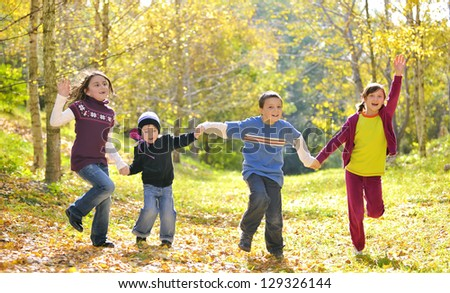 Happy kids and autumn leaves - stock photo
