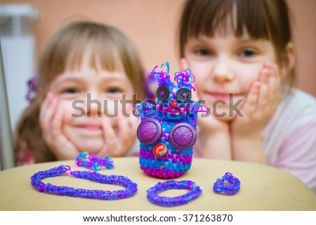 Happy kids and figurines and bracelets out of loom bands - stock photo