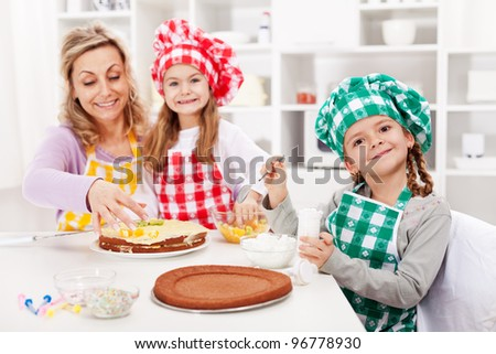 Happy kids and their mother making a cake in the kitchen - focus on the front - stock photo