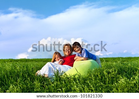 Happy kids and woman sitting outdoors in the fresh spring scenery - stock photo