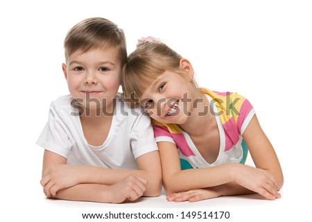 Happy kids are lying together on the floor - stock photo