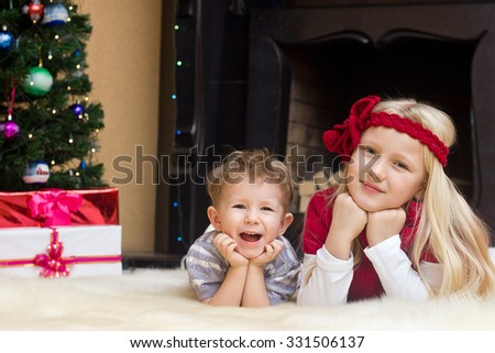 Happy kids at Christmas fir tree and fireplace