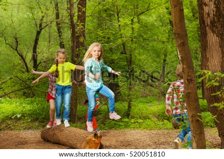 Happy kids balancing standing on the log in forest