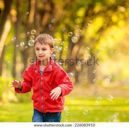 Happy kids blow bubbles outdoors - stock photo