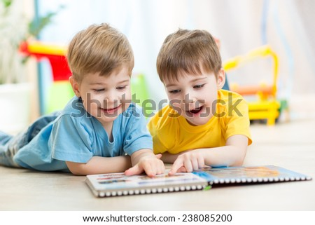 happy kids boys brothers reading together at home - stock photo