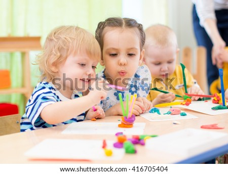 happy kids doing arts and crafts in day care centre - stock photo