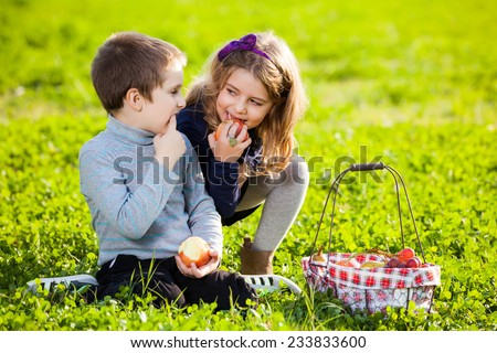 happy kids eating fruits from picnic basket sitting on the green grass - stock photo