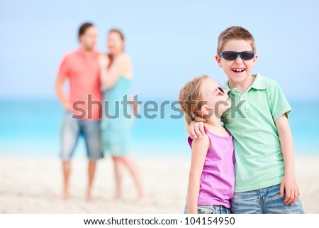 Happy kids embracing each other while parents standing on background - stock photo