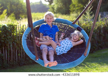 Happy kids enjoying active summer vacation. Adorable toddler girl, having fun outdoors swinging with her brother on playground in the park on a sunny day - stock photo