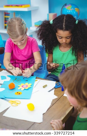 Happy kids enjoying arts and crafts painting at their desk - stock photo