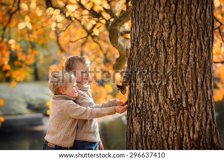 Happy kids feeds a little squirrel in autumn park - stock photo