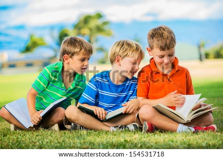 Happy Kids, Group of Young Boys Reading Books Outside Together after School - stock photo