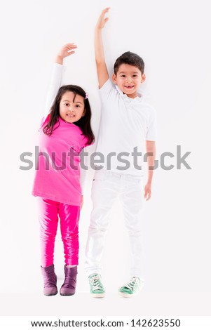 Happy kids growing up to be tall leaning against the wall - stock photo