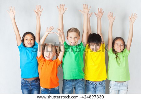 Happy kids hands up, smiling and posing at white background. - stock photo