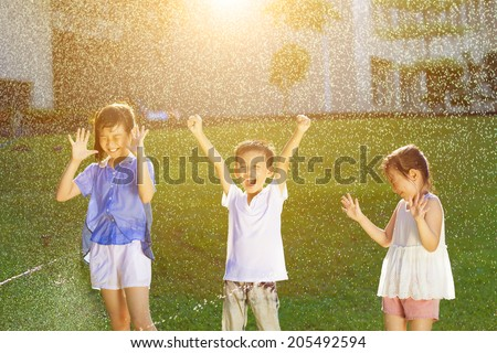Happy kids has fun playing in water fountains - stock photo