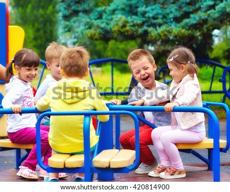 happy kids having fun on roundabout at playground - stock photo