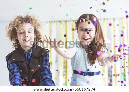 Happy kids having party, throwing colorful confetti