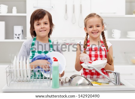Happy kids helping in the kitchen doing the dishes - stock photo