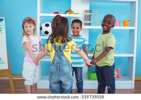 Happy kids holding hands together in the bedroom