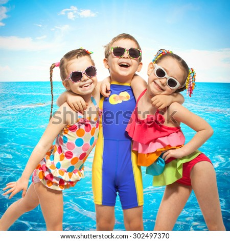Happy kids in swimsuit at sea. Fashionable, friendship concept. - stock photo