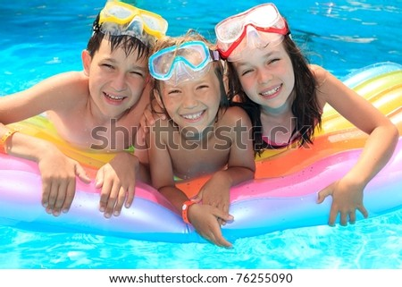 Happy kids in the pool - stock photo